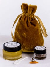 Photo of a small gold bag, AHA Peel, Botanical Buffer, and skincare application tools.