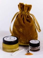 Photo of a small gold bag, AHA Peel, Botanical Buffer, and skincare application tools.